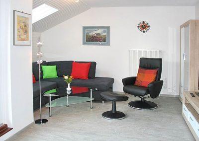 SPO-Hanack - Blick auf das gut beleuchtete Wohnzimmer mit Couch und Drehstuhl
